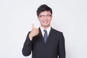 指を立ててウインクするスーツの男性